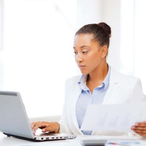 business and tax concept - african businesswoman working with computer in office